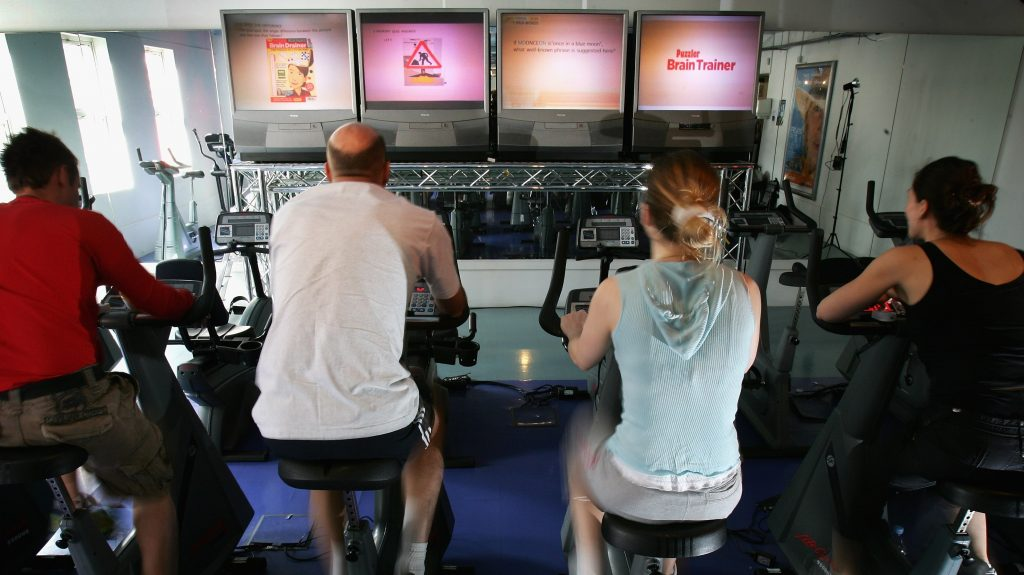 LONDON - JULY 18:  Men and women exercise in front of screens displaying puzzles and games as part of a full mind and body workout at the Fit Rooms on July 18, 2007 in London, England. Newly launched 'Puzzler Brain Train' Magazine has teamed up with the Fit Rooms in Fulham so that gym-goers can muscle up their brain power for National Brain Train Awareness Week, July 16-22.  (Photo by Chris Jackson/Getty Images)