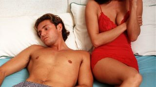 Stock Photography, Young couple laying on a bed together but turned away from each other, both looking distant and upset  (Photo by Popperfoto/Getty Images)