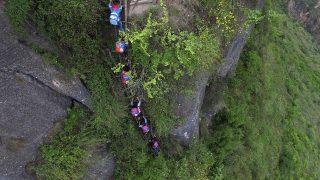 Csaocsüe, 2016. május 27.2016. május 27-én közreadott képen hazafelé tartó kisiskolások másznak egy sziklára erősített létrán a Szecsuan tartománybeli Csaocsüe megyében május 14-én. A 800 méter magas, bambuszból készített létraegyüttest a tervek szerint a közeljövőben acélra cserélik, hogy növeljék az eldugott hegyi településeken élő és onnan iskolába járó gyermekek biztonságát. (MTI/AP/Chinatopix)