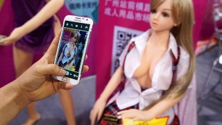 A Chinese visitor uses his smartphone to take a picture of a sex doll on display during the 2015 Guangzhou Sex Culture Festival in Guangzhou city, south China's Guangdong province, 7 November 2015.