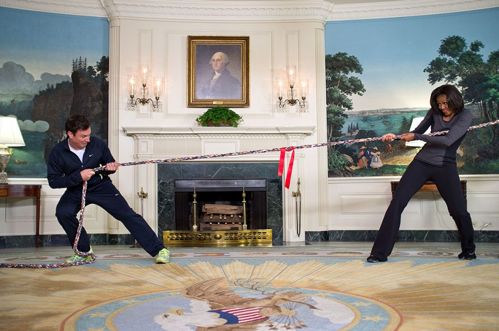 """First Lady Michelle Obama participates in a tug of war with Jimmy Fallon in the Diplomatic Reception Room of the White House during a ŇLate Night with Jimmy FallonÓ taping for the second anniversary of the """"LetŐs Move!"""" initiative, Jan. 25, 2012. (Official White House Photo by Chuck Kennedy)This official White House photograph is being made available only for publication by news organizations and/or for personal use printing by the subject(s) of the photograph. The photograph may not be manipulated in any way and may not be used in commercial or political materials, advertisements, emails, products, promotions that in any way suggests approval or endorsement of the President, the First Family, or the White House."""