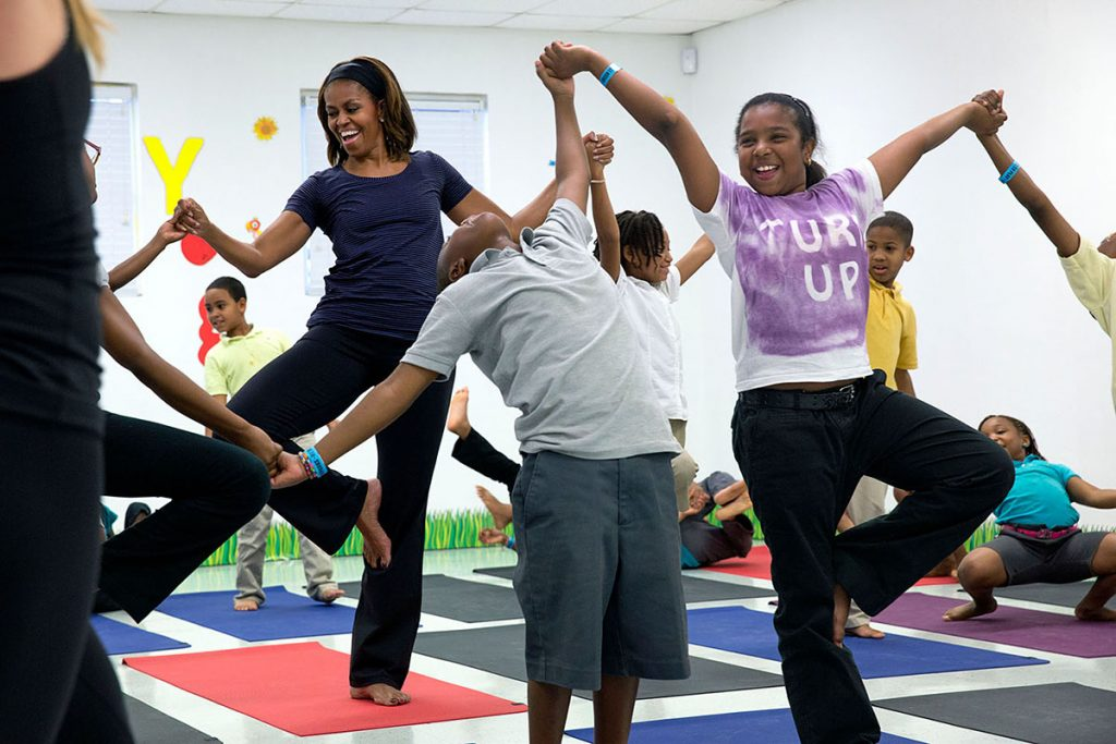 """First Lady Michelle Obama joins children for a yoga class during a """"Let's Move!"""" after school activities event at Gwen Cherry Park in Miami, Fla., Feb. 25, 2014. (Official White House Photo by Amanda Lucidon)This official White House photograph is being made available only for publication by news organizations and/or for personal use printing by the subject(s) of the photograph. The photograph may not be manipulated in any way and may not be used in commercial or political materials, advertisements, emails, products, promotions that in any way suggests approval or endorsement of the President, the First Family, or the White House."""