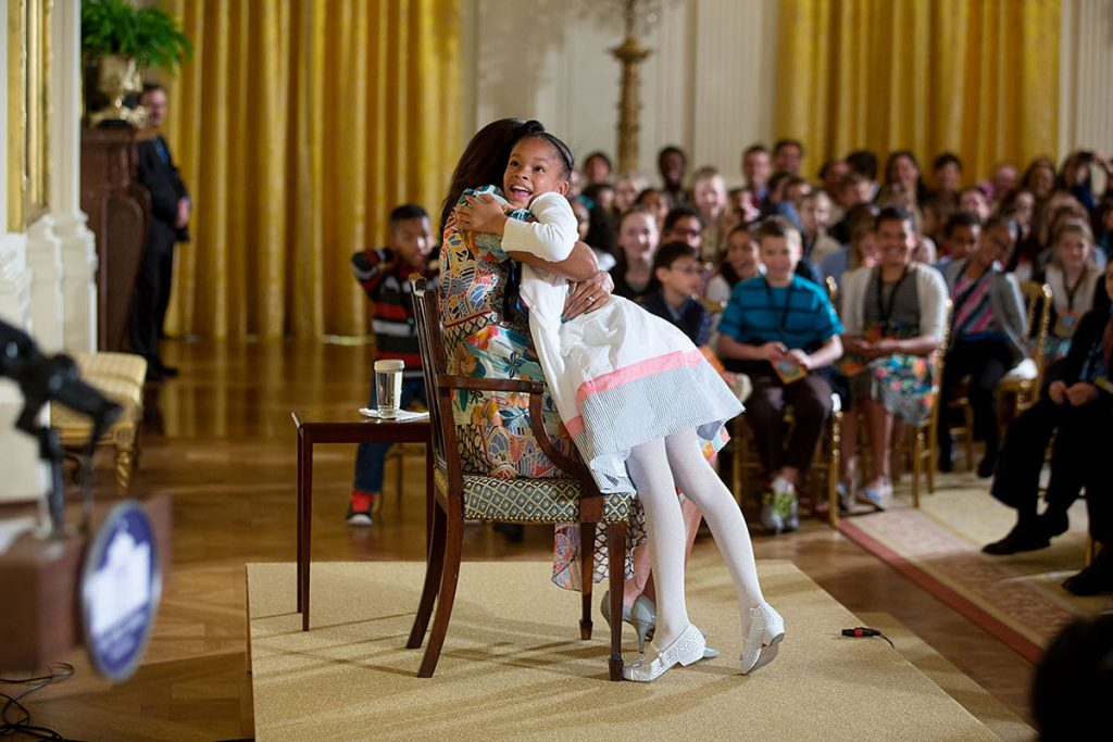 """First Lady Michelle Obama hugs a child attending the annual """"Take Our Daughters and Sons to Work Day"""" event in the East Room of the White House, April 22, 2015. (Official White House Photo by Lawrence Jackson)This official White House photograph is being made available only for publication by news organizations and/or for personal use printing by the subject(s) of the photograph. The photograph may not be manipulated in any way and may not be used in commercial or political materials, advertisements, emails, products, promotions that in any way suggests approval or endorsement of the President, the First Family, or the White House."""