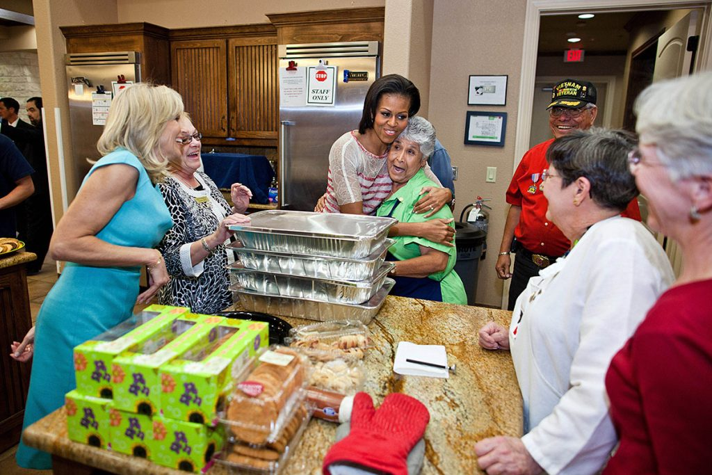 First Lady Michelle Obama, Dr. Jill Biden, and facility manager Judith Markelz, second left, greet volunteers preparing a meal at the Warrior and Family Support Center in San Antonio, Texas, April 13, 2011. The First Lady and Dr. Biden met with service members and their families during their visit to the facility, which helps care for family members of Wounded Warriors whose recovery is expected to last a long period of time. (Official White House Photo by Chuck Kennedy)This official White House photograph is being made available only for publication by news organizations and/or for personal use printing by the subject(s) of the photograph. The photograph may not be manipulated in any way and may not be used in commercial or political materials, advertisements, emails, products, promotions that in any way suggests approval or endorsement of the President, the First Family, or the White House.