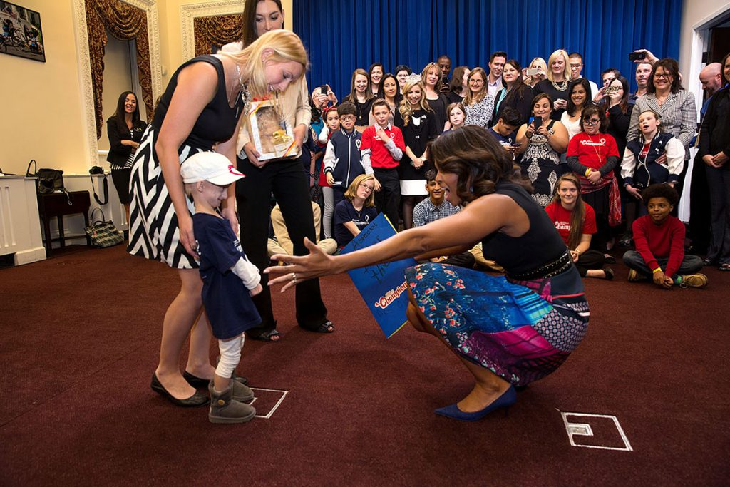 First Lady Michelle Obama reaches out to a child during a visit with children from Children's Miracle Network Hospitals, in the Eisenhower Executive Office Building of the White House, Nov. 10, 2014. (Official White House Photo by Lawrence Jackson)This official White House photograph is being made available only for publication by news organizations and/or for personal use printing by the subject(s) of the photograph. The photograph may not be manipulated in any way and may not be used in commercial or political materials, advertisements, emails, products, promotions that in any way suggests approval or endorsement of the President, the First Family, or the White House.