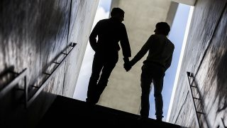 BERLIN, GERMANY - AUGUST 12: (EDITOR'S NOTE: In this photo illustration)Two men pose for a photo during walking up stairs hand in hand on August 12, 2014 in Berlin, Germany.(Photo Illustration by Thomas Trutschel/Photothek via Getty Images)