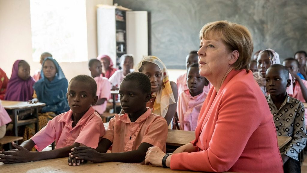 Niamey, 2016. október 10. Angela Merkel német kancellár (j) nigeri diákokkal ül a padban egy általános iskola tantermében a fõvárosban, Niameyben 2016. október 10-én. A kancellár a migrációs válság kezelésére összpontosító háromnapos afrikai körútja második állomásaként látogatott Nigerbe. (MTI/EPA/Michael Kappeler)