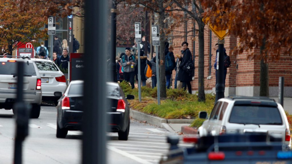Students are seen near the crime scene on the campus of Ohio State University as they respond to an active attack in Columbus, Ohio, on November 28, 2016. Eight people were injured when an attacker apparently drove into a crowd at Ohio State University on Monday, triggering an hours-long lockdown before authorities declared the campus secure. Law enforcement shot and killed one suspect, according to local television station WBNS, which reported that police led two people out in handcuffs from a garage they had surrounded on the university's main campus in Columbus.    / AFP PHOTO / Paul Vernon