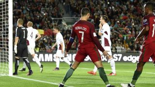 Portugal's forward Cristiano Ronaldo (C) celebrates after scoring the opening goal during the WC 2018 qualifying football match Portugal vs Latvia at the Algarve stadium in Faro on November 13, 2016. / AFP PHOTO / FRANCISCO LEONG