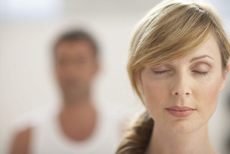 Woman with eyes closed, close-up, man in background
