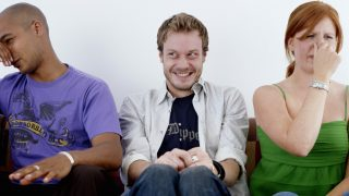 Young man, smiling, sitting between man and woman holding noses