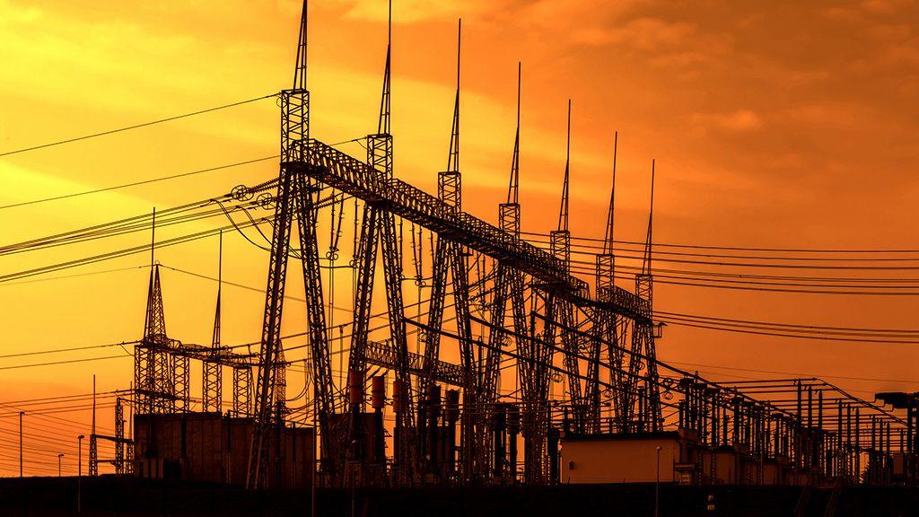 High voltage power transformer substation, sunset sky