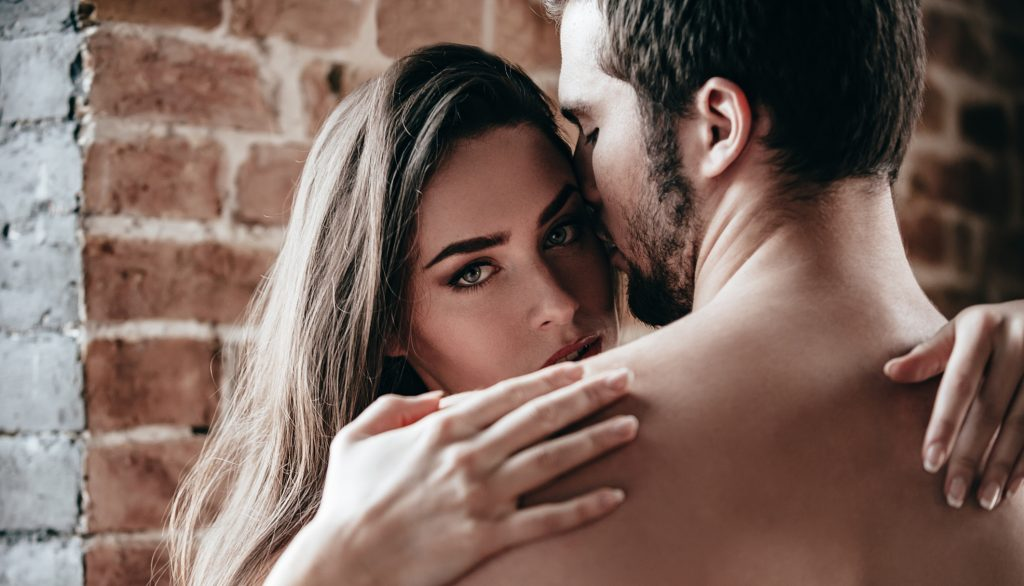 Close-up of beautiful young shirtless couple hugging while woman looking over shoulder of her boyfriend