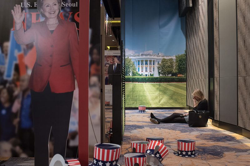 A woman sits on the floor behind a cut-outs of US presidential nominees Hillary Clinton and Donald Trump at an election event organised by the US embassy, at a hotel in Seoul on November 9, 2016.Donald Trump's stunning performance in the US presidential election triggered shock and angst in Asia, where observers fretted over the implications for everything from trade to human rights and climate change. / AFP PHOTO / Ed JONES