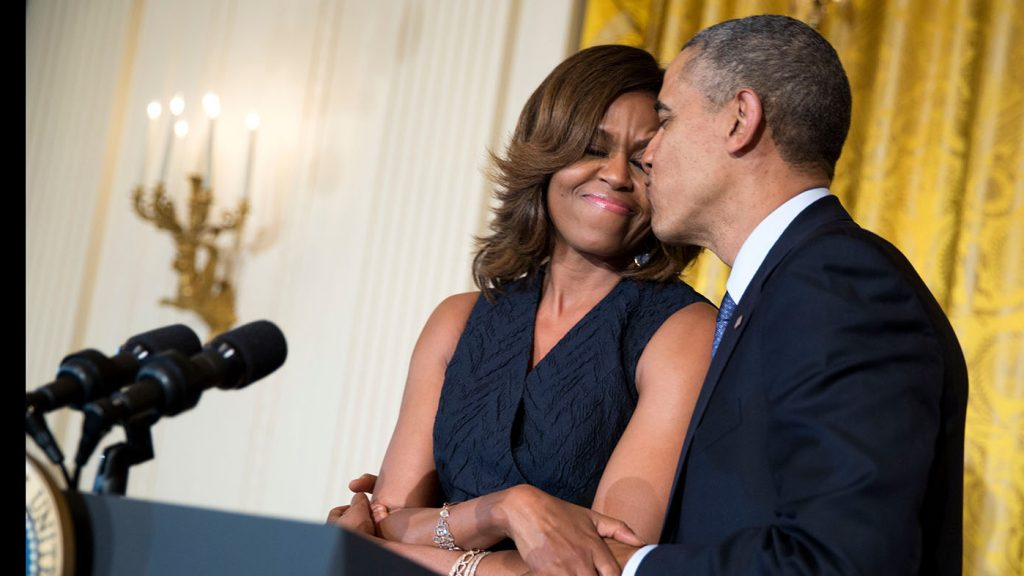President Barack Obama kisses First Lady Michelle Obama during her remarks at an Affordable Care Act reception in the East Room of the White House, May 1, 2014. (Official White House Photo by Pete Souza)This official White House photograph is being made available only for publication by news organizations and/or for personal use printing by the subject(s) of the photograph. The photograph may not be manipulated in any way and may not be used in commercial or political materials, advertisements, emails, products, promotions that in any way suggests approval or endorsement of the President, the First Family, or the White House.