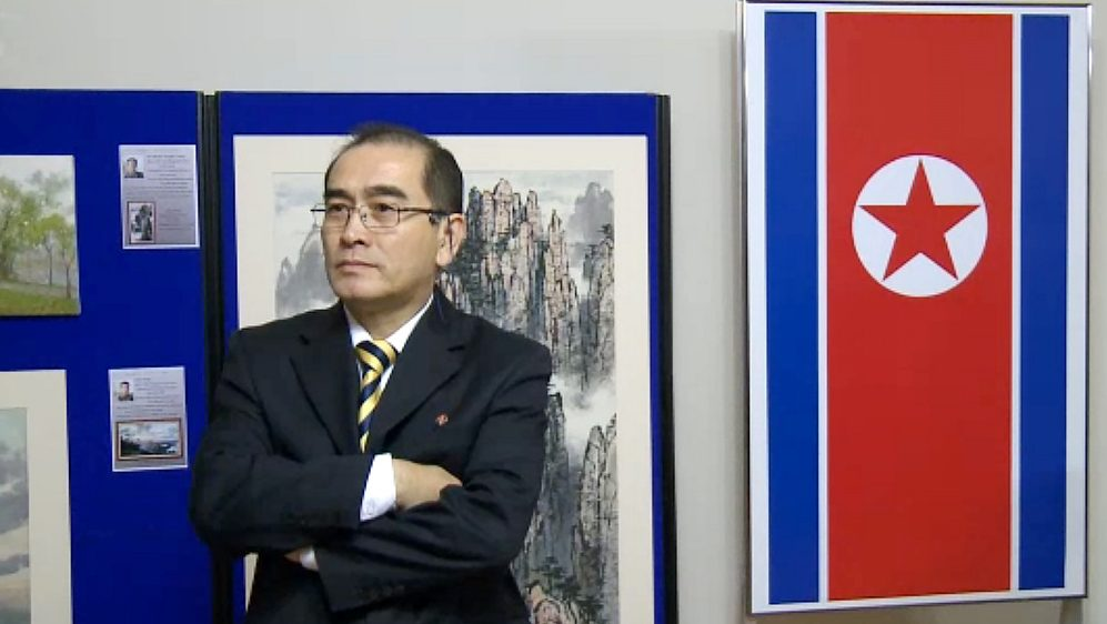 In a video grab created on August 17, 2016 taken from footage recorded by AFPTV on November 3, 2014 deputy ambassador at the North Korean embassy in London, Thae Yong-ho, stands in front of an artwork during a photocall to view an exhibition of North Korean art at the North Korean embassy in west London.  South Korea said on August 17, 2016 that North Korea's deputy ambassador to Britain Thae Yong-Ho had defected to Seoul, in a rare and major loss of diplomatic face for Pyongyang.  / AFP PHOTO / AFPTV / KATIE SCHUBAUBR