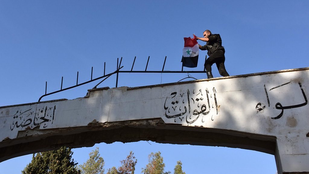 A member of the Syrian government forces holds the Syrian flag on top of the gate of the al-Moshat infantry academy on November 5, 2016 after regaining control of the area in the town of Fafeen just north of the city of Aleppo.  / AFP PHOTO / GEORGE OURFALIAN