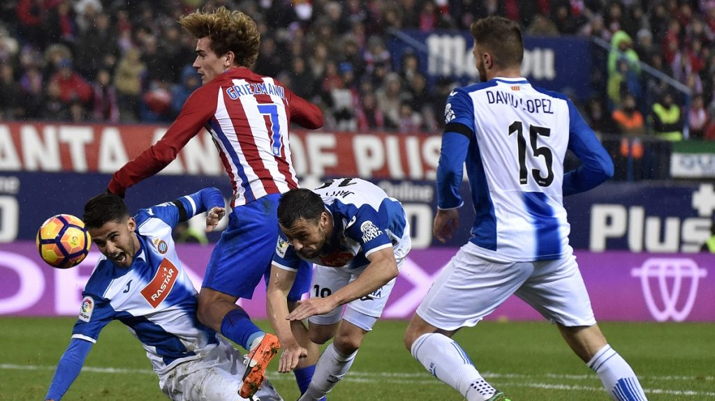 Atletico Madrid's French forward Antoine Griezmann (C) vies with Espanyol's Mexican defender Diego Reyes (L) and Espanyol's midfielder Javi Fuego (R) during the Spanish league football match Club Atletico de Madrid vs RCD Espanyol at the Vicente Calderon stadium in Madrid on December 3, 2016. / AFP PHOTO / GERARD JULIEN