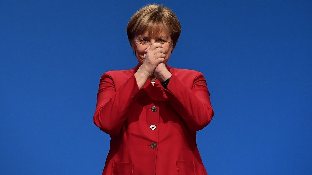 German Chancellor Angela Merkel gestures after addressing delegates during her conservative Christian Democratic Union (CDU) party's congress in Essen, western Germany, on December 6, 2016. German Chancellor Angela Merkel launches into campaign mode for elections taking place in 2017. / AFP PHOTO / TOBIAS SCHWARZ