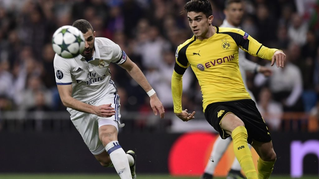 Real Madrid's French forward Karim Benzema (L) vies with Dortmund's Spanish defender Marc Bartra during the UEFA Champions League football match Real Madrid CF vs Borussia Dortmund at the Santiago Bernabeu stadium in Madrid on December 7, 2016. / AFP PHOTO / JAVIER SORIANO
