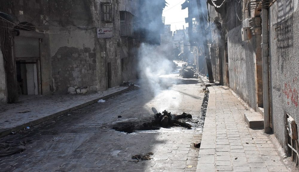 """EDITORS NOTE: Graphic content / The charred body of a rebel fighter lie on a street in the Bab al-Hadid neighbourhood, in Aleppo's Old City, on December 8, 2016, after Syrian pro-government forces took control of the area. President Bashar al-Assad said victory for his forces in Aleppo would be a """"huge step"""" in ending Syria's war, as government troops battled to retake more rebel ground. Regime forces have retaken about 80 percent of former rebel territory in Aleppo since launching an all-out offensive three weeks ago to recapture Syria's second city.   / AFP PHOTO / GEORGE OURFALIAN"""