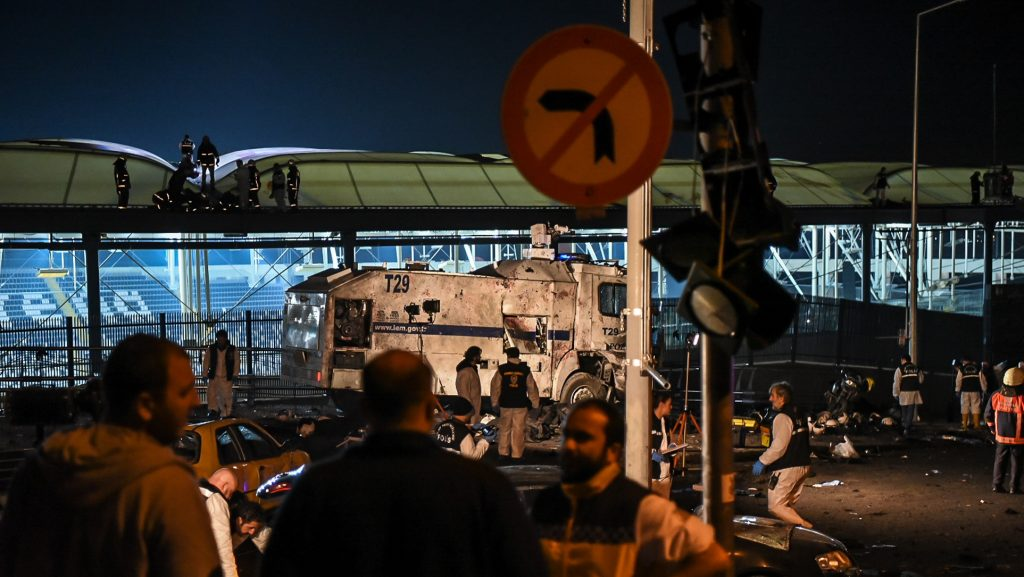 Forensic officers work as emergency officers walk with bodybags on the roof of the Vodafone Arena stadium at the site where a car bomb exploded near the stadium of football club Besiktas in central Istanbul on December 10, 2016.   Twenty-nine people, mainly police, were killed and 166 wounded in Istanbul on Saturday when twin bombings struck the heart of the city close to the stadium of top flight football giants Besiktas after a major game. / AFP PHOTO / Ozan KOSE