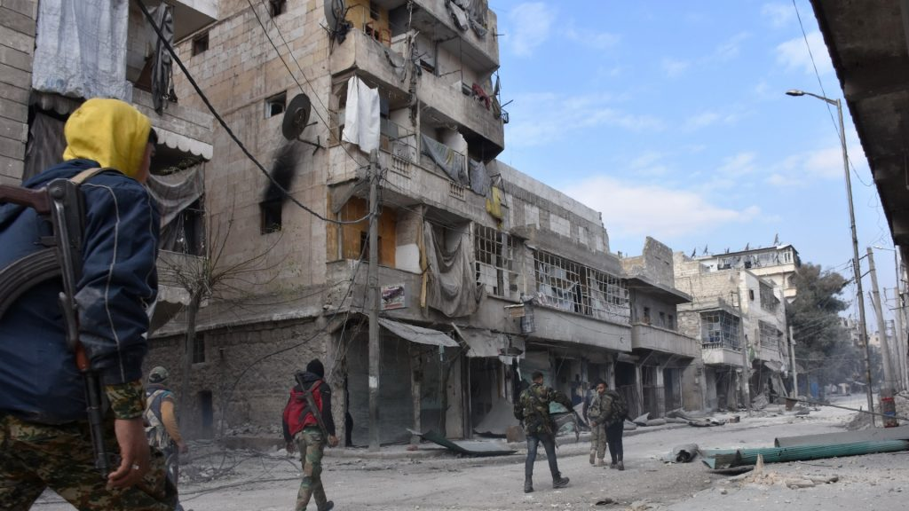Syrian pro-government forces patrol Aleppo's eastern al-Salihin neighbourhood on December 12, 2016 after troops retook the area from rebel fighters. / AFP PHOTO / GEORGE OURFALIAN