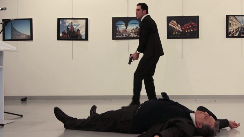 """EDITORS NOTE: Graphic content / This picture taken on December 19, 2016 shows Andrey Karlov (R), the Russian ambassador to Ankara, lying on the floor after being shot by a gunman (C) during an attack during a public event in Ankara. A gunman crying """"Aleppo"""" and """"revenge"""" shot Karlov while he was visiting an art exhibition in Ankara on December 19, witnesses and media reports said. The Turkish state-run Anadolu news agency said the gunman had been """"neutralised"""" in a police operation, without giving further details. / AFP PHOTO / Hurryet / Hasim KILIC / Turkey OUT"""