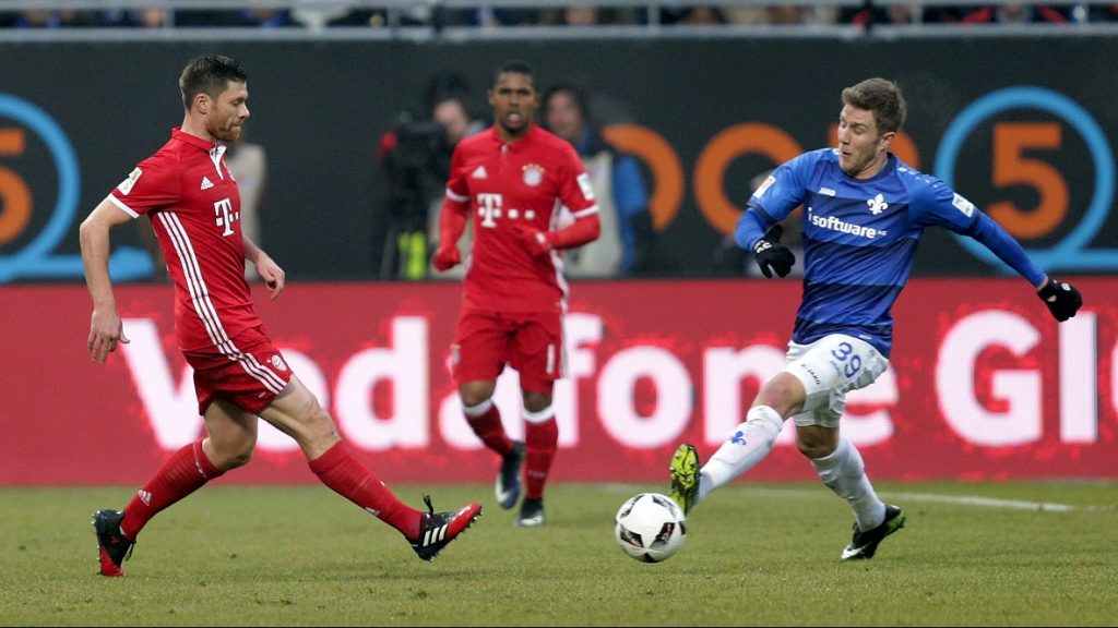 Darmstadt's Sven Schipplock (r) and Munich's Xabi Alonso compete for the ball during the Bundesliga soccer match between Darmstadt 98 and Bayern Munich at Jonathan Heimes stadium in Darmstadst, Germany, 18 December 2016. Photo: Hasan Bratic/dpa