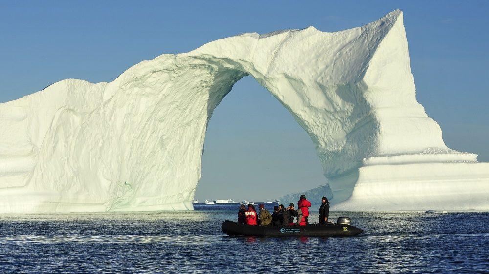 Denmark. Greenland. West coast. Zodiac near an arch shaped iceberg in the straight of Vaigat.    Biosphoto / Antoine Lorgnier
