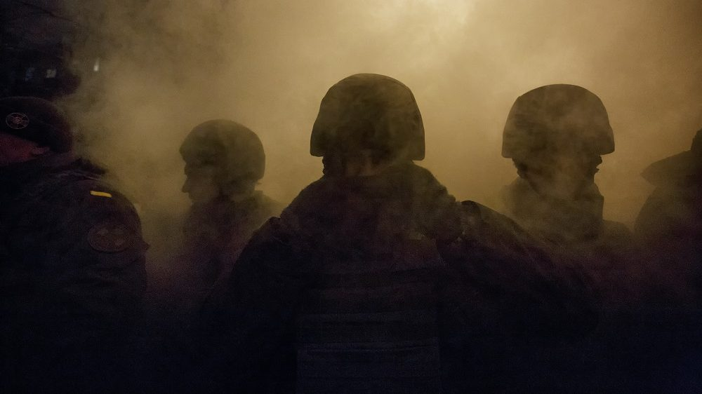 A police line stand in front of the Presidential office as smoke of smoke grenade hangs behind during a rally of activists and supporters of Ukrainian nationalist in downtown Kyiv, Ukraine, 01 December 2016. Activists gathered to mark the third anniversary of the first clashes protesters with police on 01 December 2013 during Euromaidan Revolution in Kyiv and to demand from the government to free the political prisoners.  (Photo by Maxym Marusenko/NurPhoto)