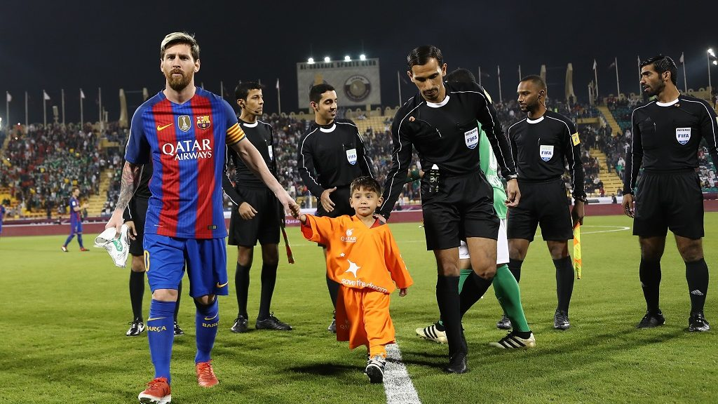 FC Barcelona Lionel Messi (L) holds the hands of Afghan boy Murtaza Ahmadi on the pitch before the start of a friendly football match against Saudi Arabia's Al-Ahli FC on December 13, 2016 in the Qatari capital Doha.  Barcelona play Saudi champions Al-Ahli in a friendly in Doha, the Spanish club's last major obligation of its four year shirt sponsorship deal with Qatar Airways.   / AFP PHOTO / KARIM JAAFAR