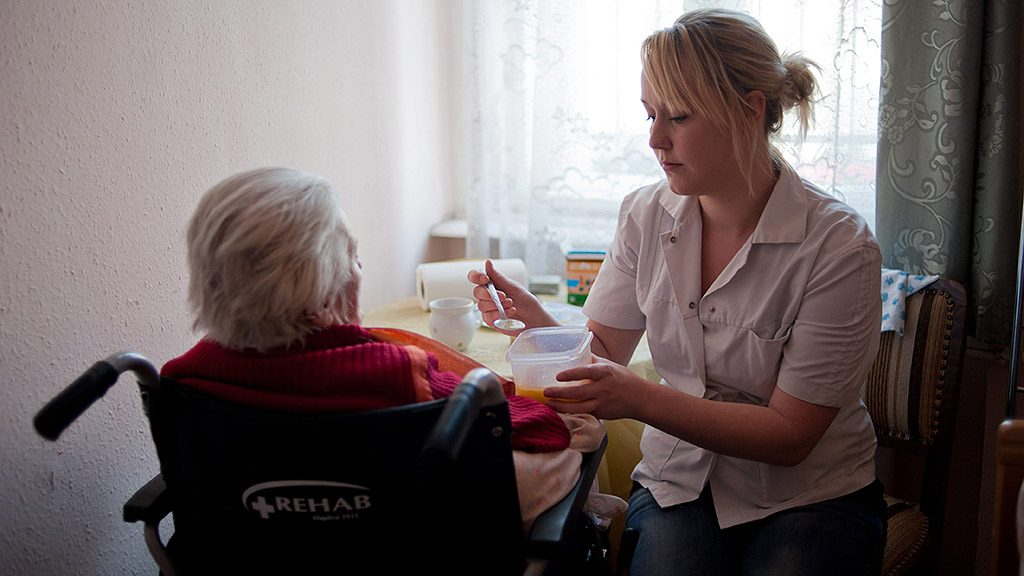 Budapest, 2012. március 27.Egy gondozó egy idős asszonyt etet a szobájában a Mátyás téri Arany Alkony idősotthonban, ahol 85 idős embert gondoznak. Az intézményt 1996-ban hozták létre, amelyben a szociális alapellátást a Kálvin János Presbiteri Misszió végzi, az egészségügyi szolgáltatásokért és az ingatlannal kapcsolatos pénzügyi kötelezettségekért a Medicatus cégcsoport felel.MTI Fotó: Kallos Bea