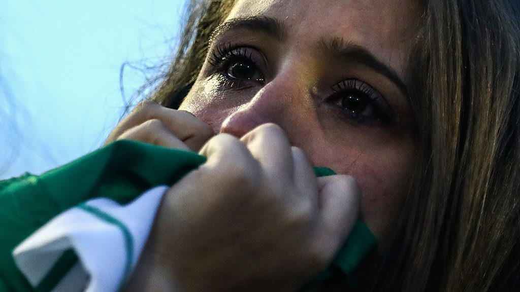 CHAPECO, BRAZIL - NOVEMBER 30:  A fan cries while paying tribute to the players of Brazilian team Chapecoense Real at the club's Arena Conda stadium in Chapeco, in the southern Brazilian state of Santa Catarina, on November 30, 2016. The players were killed in a plane accident in the Colombian mountains. Players of the Chapecoense team were among the 77 people on board the doomed flight that crashed into mountains in northwestern Colombia. Officials said just six people were thought to have survived, including three of the players. Chapecoense had risen from obscurity to make it to the Copa Sudamericana finals scheduled for Wednesday against Atletico Nacional of Colombia.  (Photo by Buda Mendes/Getty Images)