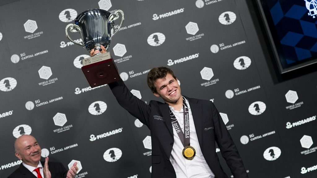 Magnus Carlsen, Norwegian chess grandmaster and current World Chess Champion, hods up his trophy during a closing ceremony after defeated Sergey Karjakin, Russian chess grandmaster, at the World Chess Championship on November 30, 2016 in New York. / AFP PHOTO / Eduardo Munoz Alvarez