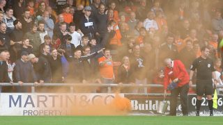 CREWE, ENGLAND - SEPTEMBER 24:  A steward deals with a flare set off by Blackpool fans during the Sky Bet League Two match between Crewe Alexandra and Blackpool at The Alexandra Stadium on September 24, 2016 in Crewe, England. (Photo by Stephen White/CameraSport via Getty Images)