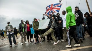 Protesters and refugees are blocked by police at the entrance of the jungle. English flags waved by refugees in Calais, France, October 2016. 1s pro-refugee demonstration was banned by the prefecture. The rally was held but the police pushed the refugees in the jungle with tear gas and a water cannon. (Photo by Julien Pitinome/NurPhoto via Getty Images)