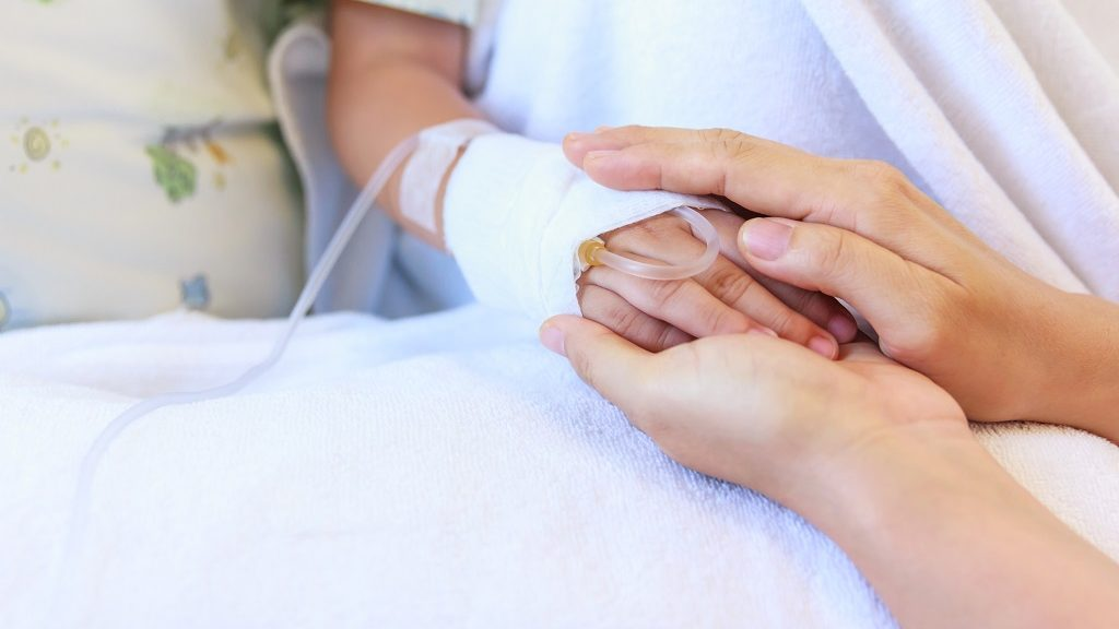 Close up hand of parent holding hand of child in hospital, saline intravenous (IV) on hand, shallow depth of field (DOF) saline intravenous (IV) in focus.