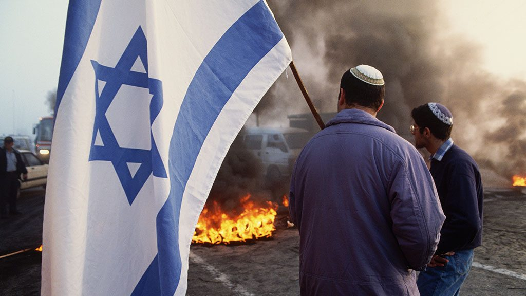 A Jewish man carries an Israeli flag at a demonstration against killings of settlers by Palestinians.   (Photo by Peter Turnley/Corbis/VCG via Getty Images)