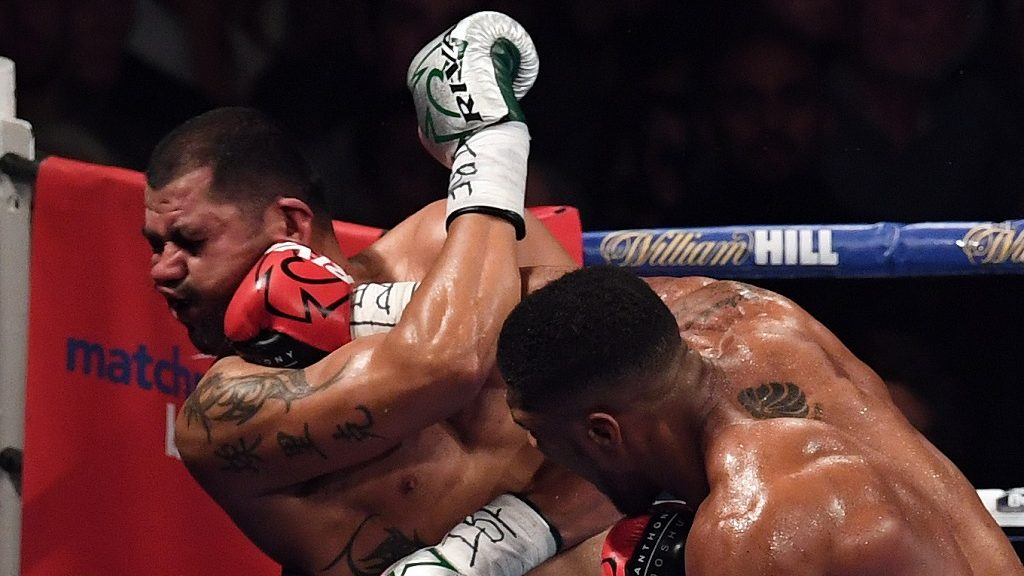 England's Anthony Joshua (R) delivers the winning punch against  USA's Eric Molina during the IBF World Heavyweight Championship boxing match in Manchester, north-west England on December 10, 2016.   / AFP PHOTO / Paul ELLIS