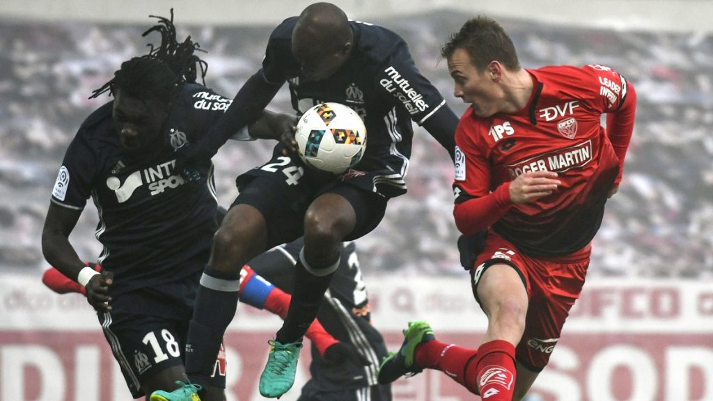 Dijon's Hungarian defender Adam Lang (R) vies with Olympique de Marseille's French defender Rod Fanni (C) and Olympique de Marseille's French forward Bafetimbi Gomis during the French L1 football match Dijon (DFCO) vs Marseille (OM) on December 10, 2016 at the Gaston-Gerard stadium in Dijon.  / AFP PHOTO / JEFF PACHOUD