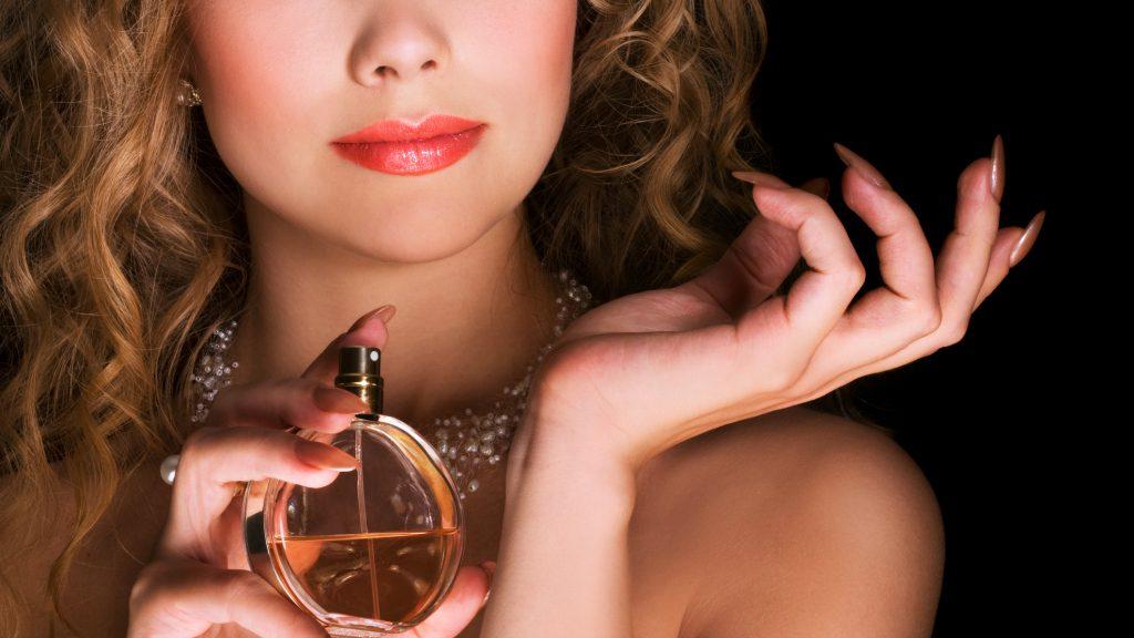 Beautiful woman applying perfume on her wrist