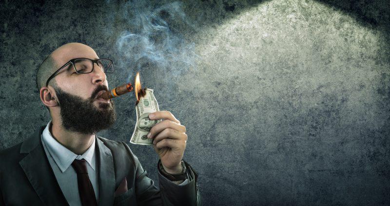 burn wealth concept: adult burning a $ 100 bill
