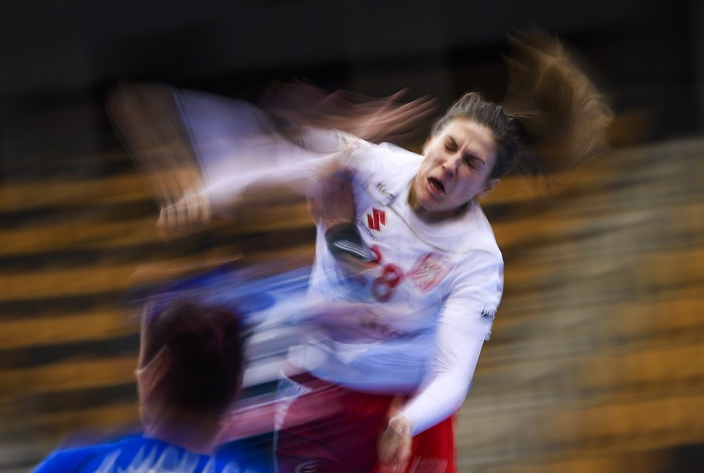 Poland's Alina Wojtas is stoped by a French player during the Women's European Handball Championship Group B match between France and Poland in Kristianstad, Sweden on December 4, 2016. / AFP PHOTO / JONATHAN NACKSTRAND