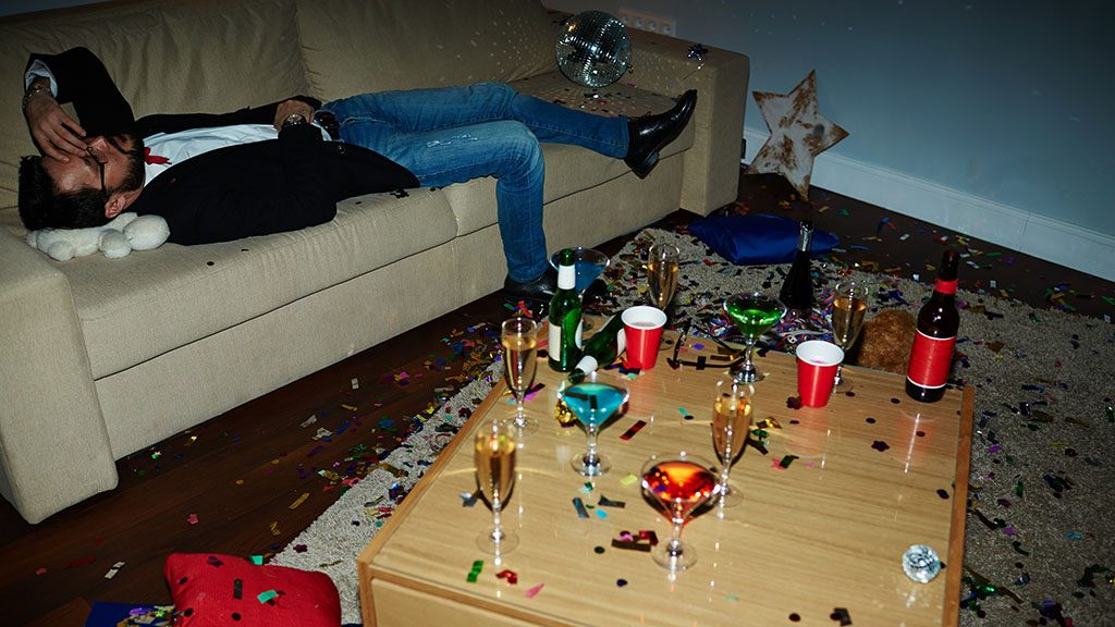 Exhausted man lying on sofa after tiresome party