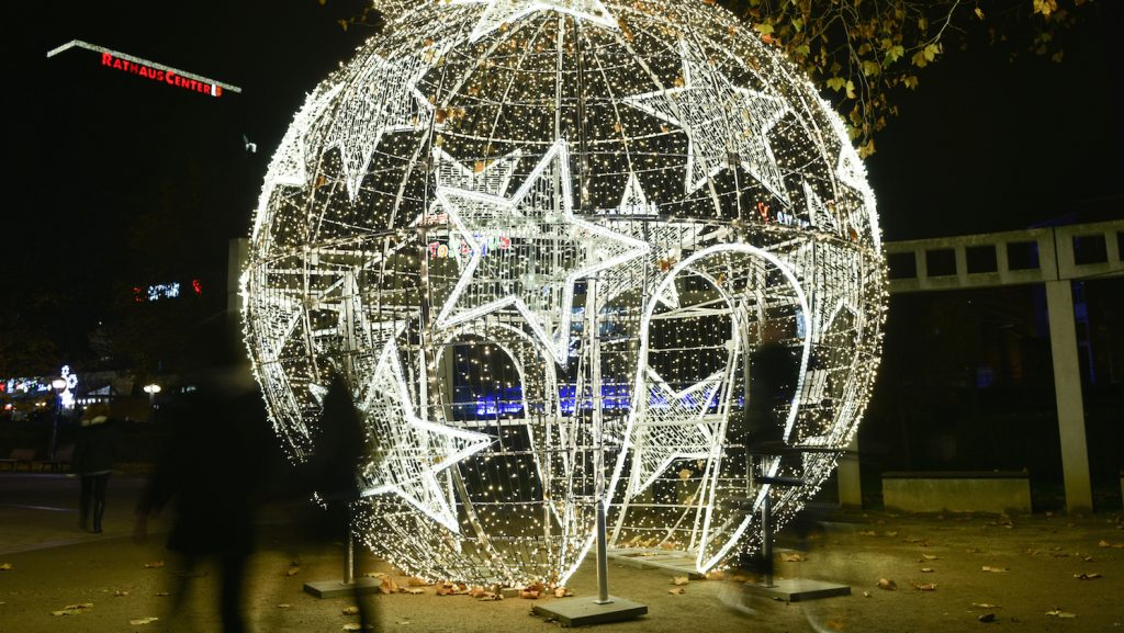 Visitors walk through a five-meter high lighted Christmas ball in Ludwigshafen, Germany, 24 November 2014. According to the city, it is the largest of its kind in Germany. About 20,000 LED lights are attached. Photo: UWE ANSPACH/dpa