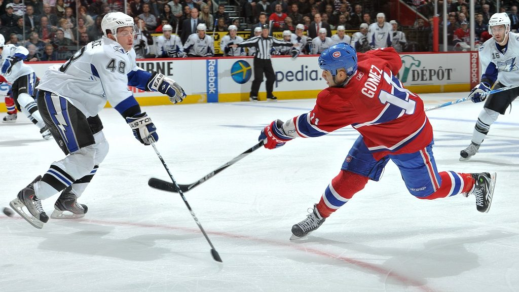 MONTREAL, QC - OCTOBER 13:  Scott Gomez #11 of the Montreal Canadiens takes a shot through Mike Vernace #48 of the Tampa Bay Lightning during the NHL game on October 13, 2010 at the Bell Centre in Montreal, Quebec, Canada. (Photo by Francois Lacasse/NHLI via Getty Images)