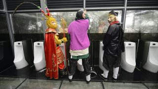 This picture taken on November 19, 2016 shows cosplay actors posing for photos in a glass public toilet to mark World Toilet Day in Changsha in China's central Hunan province.   The World Toilet Organisation holds an annual World Toilet Day on November 19 to raise awareness of toilet hygiene and sanitation. / AFP PHOTO / STR / China OUT
