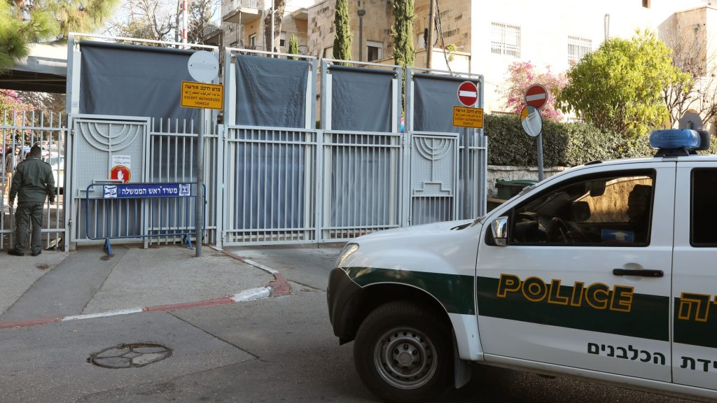 An Israeli police car is seen at the entrance to the residence of Israeli Prime Minister Benjamin Netanyahu as members of the media wait for the arrival of police investigators on January 2, 2017. Israeli police were expected to question Prime Minister Benjamin Netanyahu earlier in the day over whether he illegally accepted gifts from wealthy supporters, media reports said, in a probe shaking the country's political scene.  / AFP PHOTO / GALI TIBBON