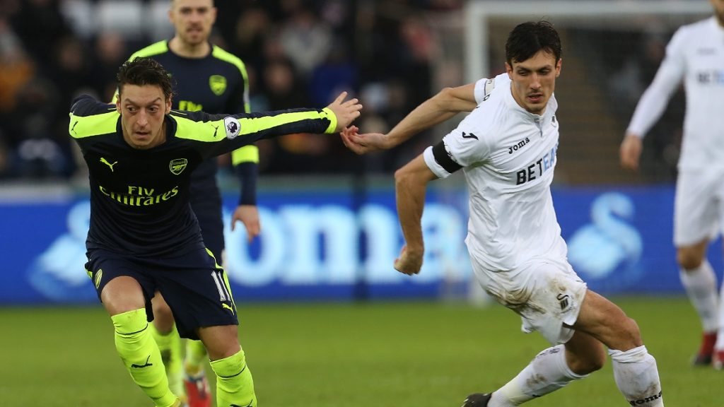 Arsenal's German midfielder Mesut Ozil (L) loses Swansea City's English midfielder Jack Cork during the English Premier League football match between Swansea City and Arsenal at The Liberty Stadium in Swansea, south Wales on January 14, 2017. / AFP PHOTO / Geoff CADDICK / RESTRICTED TO EDITORIAL USE. No use with unauthorized audio, video, data, fixture lists, club/league logos or 'live' services. Online in-match use limited to 75 images, no video emulation. No use in betting, games or single club/league/player publications.  /